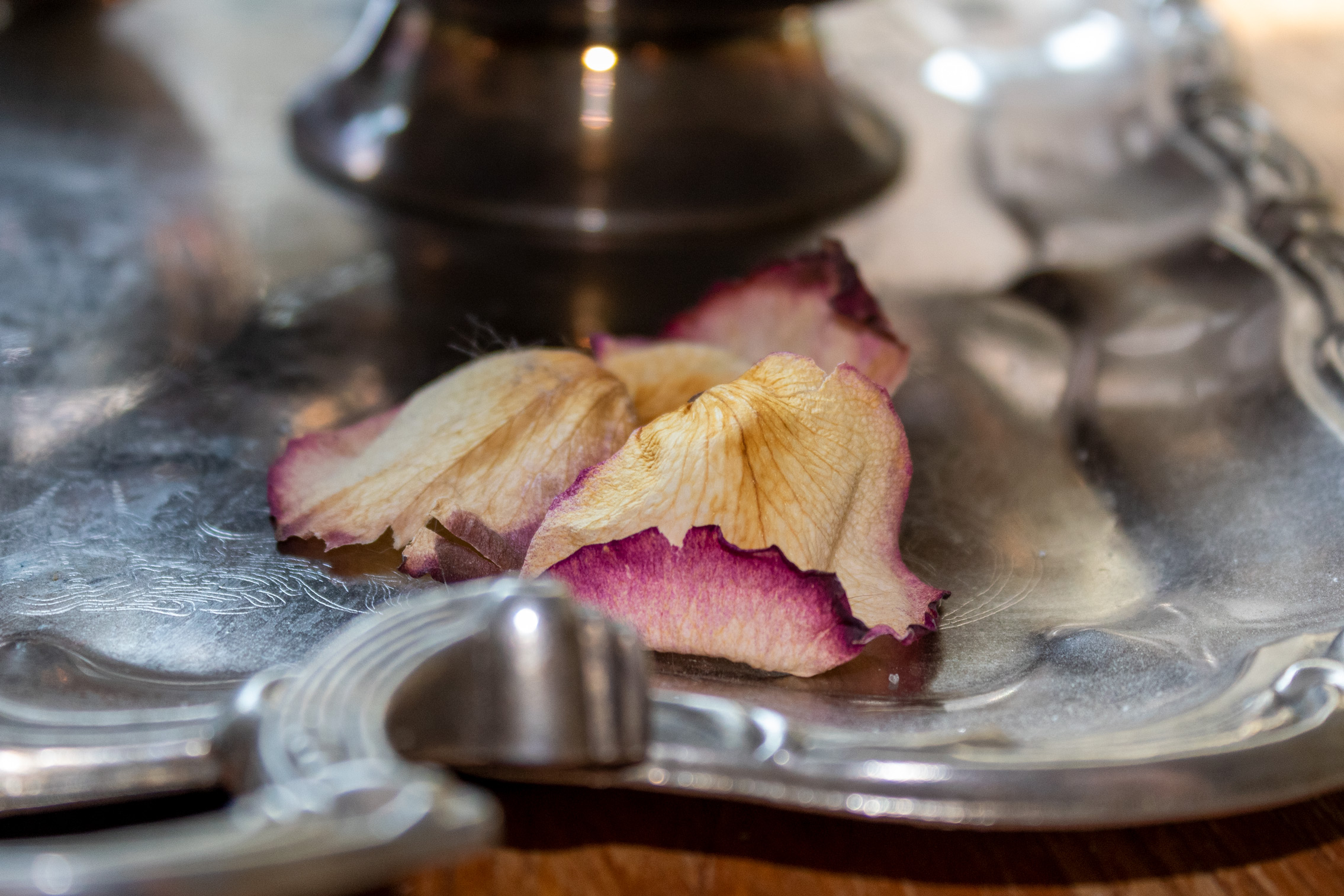 Faded rose petals sitting on a silver tea tray