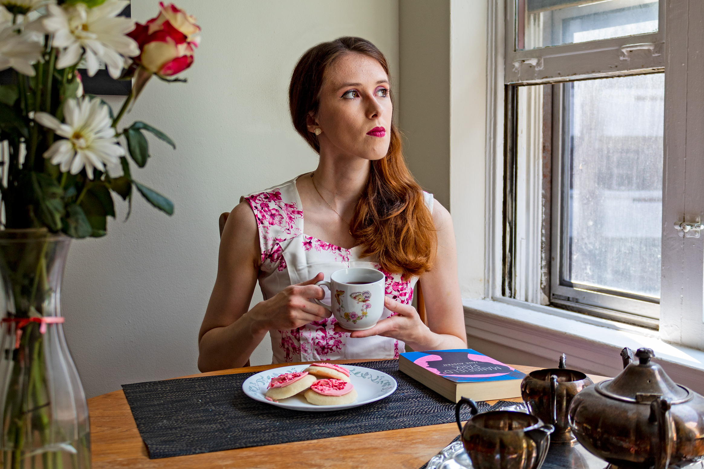 Woman holding a tea cup and gazing out of a window; in front of her are cookies and a book