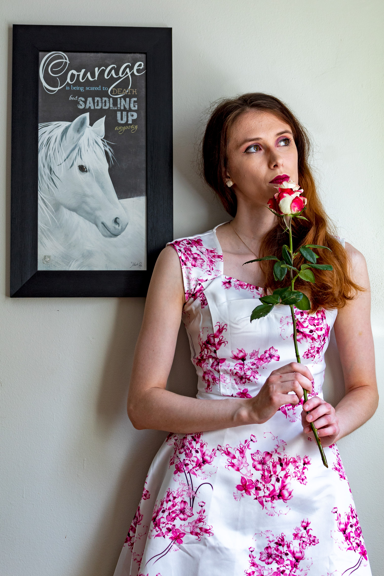 "Woman standing with a rose in her hands; beside her is a picture with a horse that says ""Courage is being scared to death but saddling up anyway"""