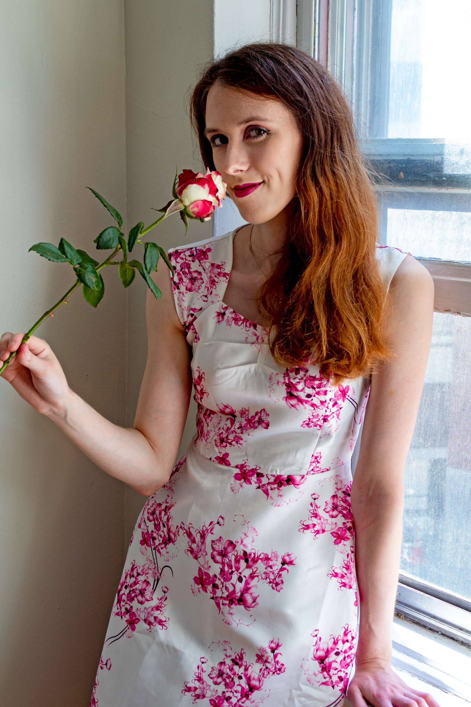 Woman leaning against a window while holding a rose up to her nose