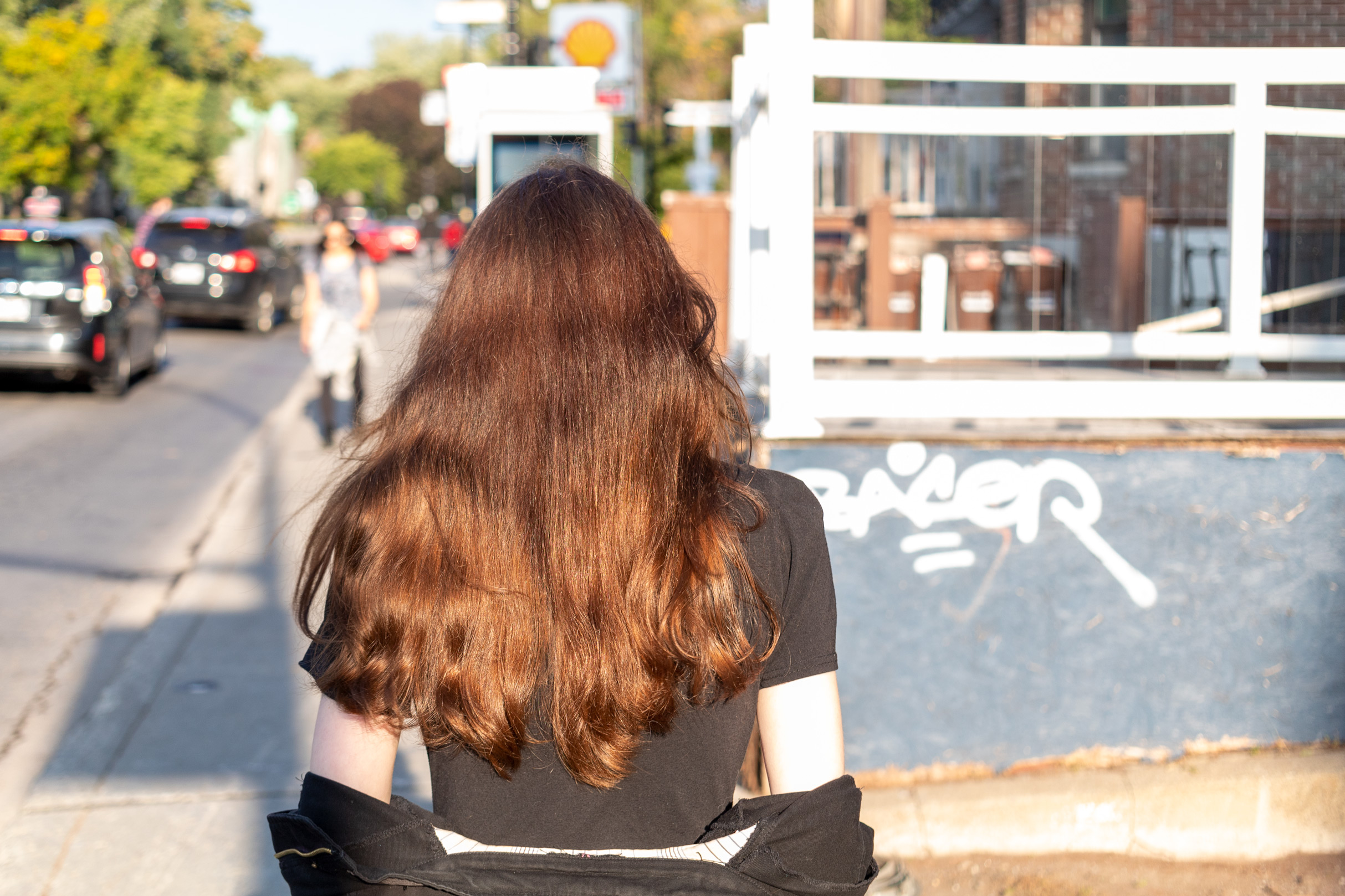 Woman with long brown hair reflecting the sunlight walking down a street