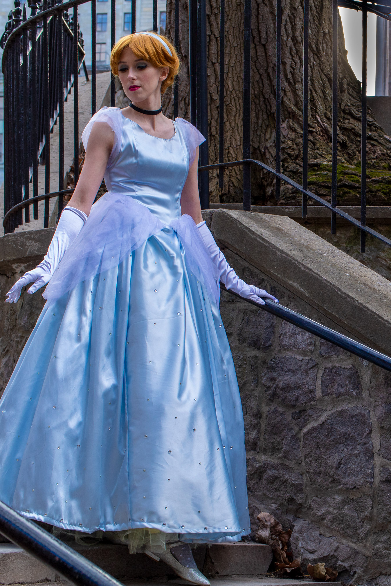 Woman dressed as Cinderella walking down a staircase