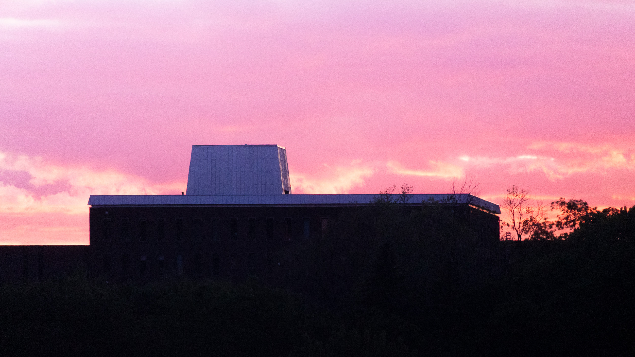 A building backlit with the pink glow of a sunset sky